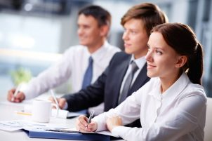 15296983 - three business people sitting at seminar, the focus is on woman