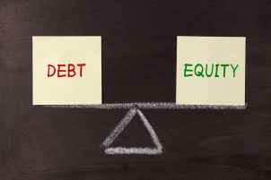Debt and Equity Balance concept on blackboard.